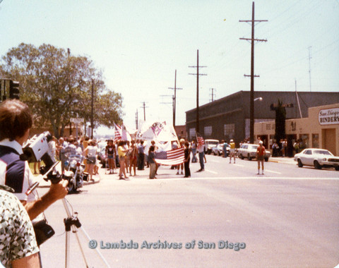 P109.027m.r.t San Diego Pride Parade 1978: Across street from front of parade with prominent USA flags.