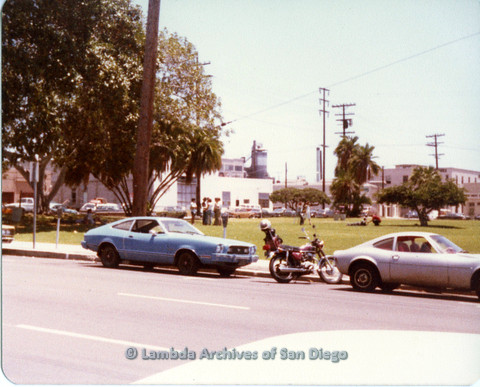 P109.041m.r.t San Diego Pride Parade 1978 View from park, two cars and a motorcycle parked.