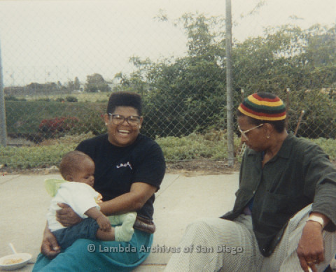 P125.020m.r.t Phyllis Jackson holding Nakia Taylor while sitting with Marti Mackey during Pride 1991