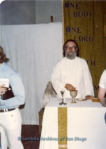 P110.050m.r.t Metropolitan Community Church: Joseph Gilbert standing behind table with chalice.
