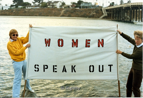 "P104.017m.r.t Dignity San Diego: Two women by the ocean, holding a sign that reads ""WOMEN SPEAK OUT"""