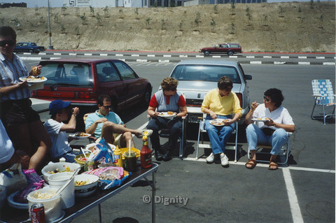 P104.069m.r.t Dignity San Diego: Group of people eating picnic fare at a parking lot