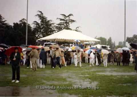 P024.550m.r.t People with umbrellas around white tent