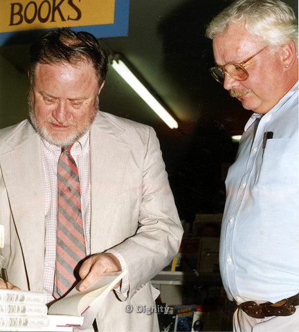 "P104.169m.r.t Dignity San Diego: Author John McNeil on left signing book ""Taking A Chance on God""  while another man looks on."