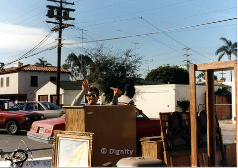 P104.008m.r.t Dignity church and MCC yard sale: two men behind wooden furniture, with one man smiling towards camera