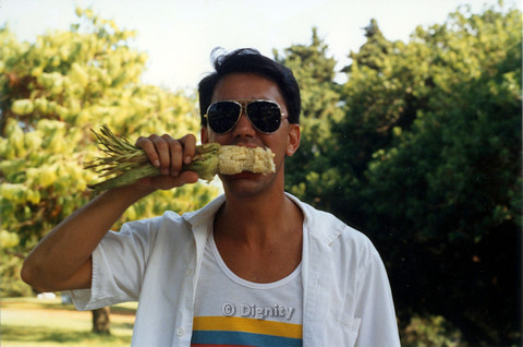 P104.202m.r.t Dignity San Diego: Rick Duffer eating corn on cob wearing aviator sunglasses in front of trees