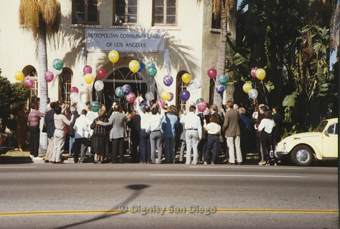 "P103.101m.r.t Group of people holding balloons, with white banner above ""Metropolitan Community Church of Los Angeles"