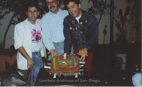 P001.157m.r.t 1st Anniversary: 3 men posing with cake.