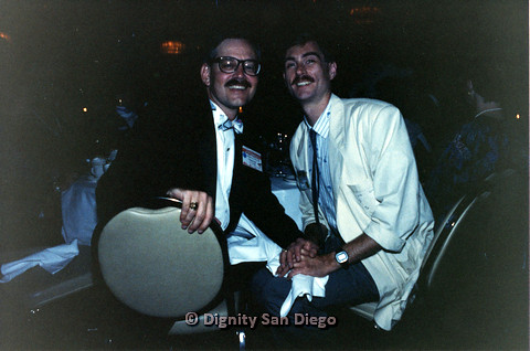 P103.126m.r.t Dignity Ninth Biennial Convention, San Francisco 1989: Two men sitting closely together, smiling at camera