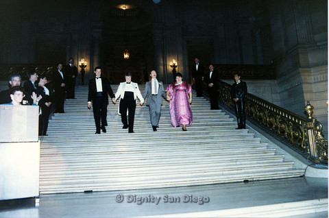 P103.116m.r.t Dignity Ninth Biennial Convention 1989: Men and women in formalwear holding hands and walking down the stairs