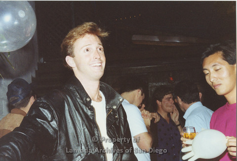 P001.168m.r.t 1st Anniversary 1991: Man in a black jacket, another man holding an inflated latex glove