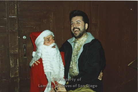 P001.296m.r.t X-mas: man in black jacket and wearing a black ring sitting on Santa's lap