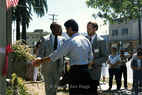 P103.174m.r.t San Diego Dignity Center: Leon Williams and Henry Ramirez cutting ribbon at front of Center, Bruce Neveu on right
