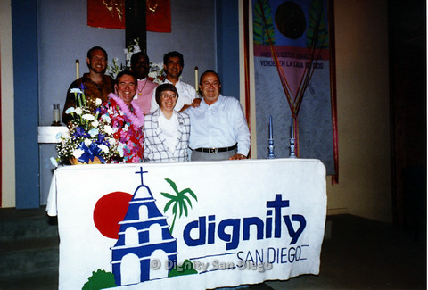 P103.142m.r.t Left to right: unknown man, Pat McArron, Stan Lewis, Lucy, two unknown men, in front of Dignity San Diego banner