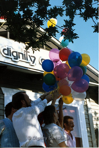 P103.181m.r.t San Diego Dignity Center: Group of people holding balloon bouquet in front of Center with Bruce Neveu at front