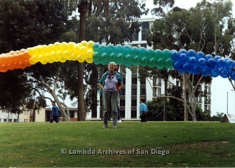 P024.439m.r.t 1989 San Diego Pride Parade: Sally Hopkins standing in front of a rainbow balloon arrangment.