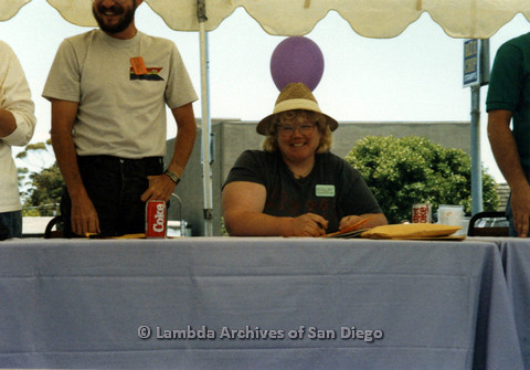 P024.431m.r.t 1990 San Diego Pride festival: Woman wearing a hat and glasses behind a table