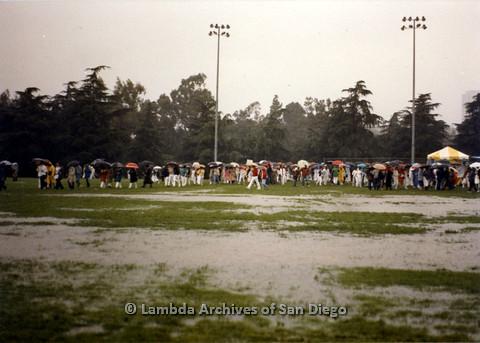 P024.549m.r.t  People on field holding umbrellas