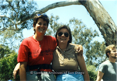 P024.528m.r.t 1990 San Diego Pride: Woman in red San Diego Lesbian Press shirt with her arm around another woman