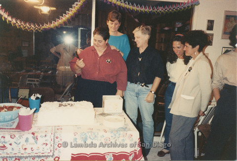 P024.377m.r.t Edna Myers (center) prepares to cut a cake while Judith McConnell (rear, second from left), Sally Hopkins (third from left), and other women look on.
