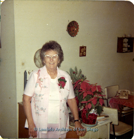 P110.002m.r.t Metropolitan Community Church: Lovedy Gilbert smiling at camera in front of table with poinsettias.