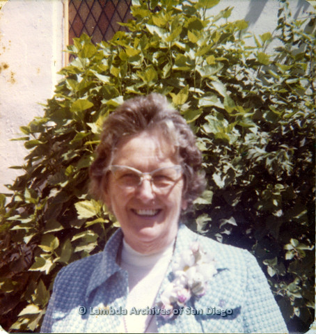 P110.001m.r.t Metropolitan Community Church: Lovedy Gilbert smiling at camera outside with plant backdrop.