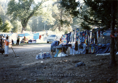 P024.228m.r.t Tables set up with numerous tie-dye articles of clothing.