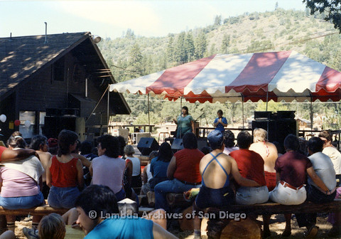 P024.226m.r.t A woman speaking in to a microphone and an ASL translator on the Day stage.