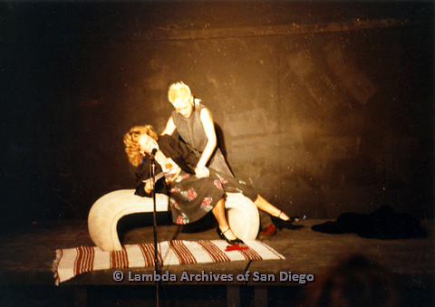 P024.201m.r.t Ellie Rapp laying back on bench while Laura Sutherland  touches her inner thigh