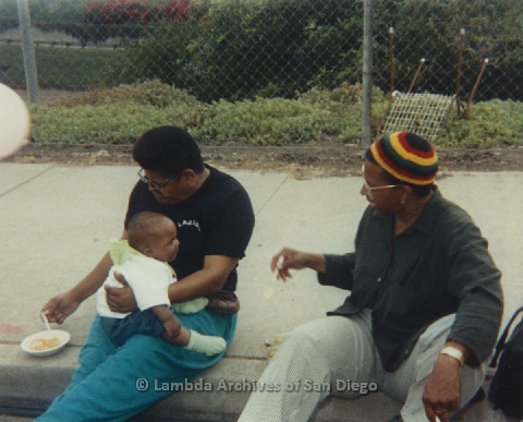 P125.021m.r.t Phyllis Jackson eating while holding Nakia Taylor alonside Marti Mackey during Pride 1991