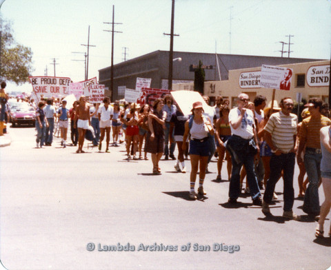 "P109.026m.r.t San Diego Pride Parade 1978: In the midst of parade with prominent Be Proud… Save Our…"" banner."