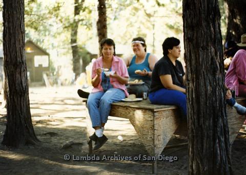 P024.292m.r.t Susan Fleming (left) and partner Sally Garrett (right) sitting on elevated platform eating food