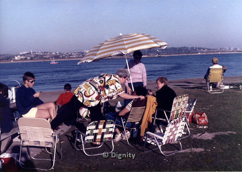P104.028m.r.t Dignity San Diego: Women sitting under beach umbrella, looking at the water