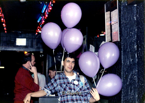 P104.189m.r.t Dignity San Diego: Rick Duffer holding 3 purple balloons with 4 more behind him. 3 people in background