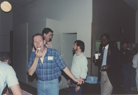 P104.080m.r.t Dignity San Diego: Stan Lewis (in blazer and tie) smiling at camera, surrounded with unidentified men