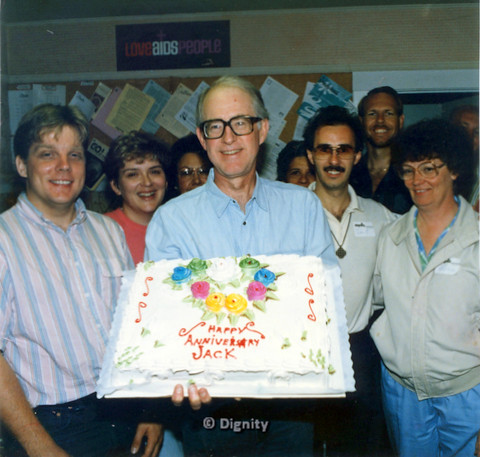 "P104.077m.r.t Dignity San Diego: Jack Shuk holding cake with words "" Happy Anniversary Jack"" while surrounded by Dignity people. Including Bruce Neveu (back right), John M. (wearing tag front of Bruce in beige), and Michelle (wearing tag next to John)"