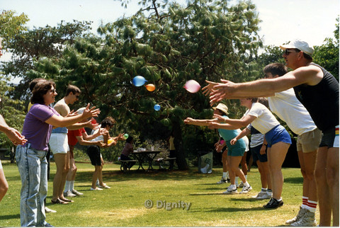 P104.050m.r.t Dignity Picnic 4th of July: Men and wome tossing water balloons to each other, across a few feet