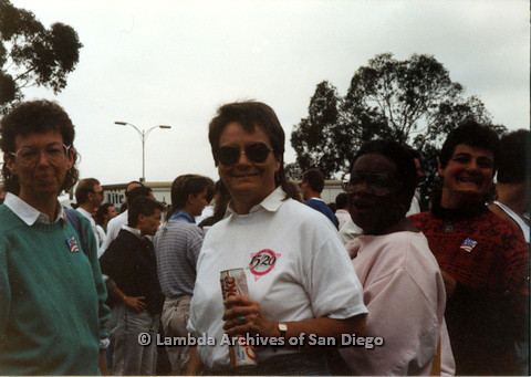 P024.437m.r.t 1990 San Diego Pride Parade:Unknown people smiling for the camera. Woman in center holding two diet coke cans