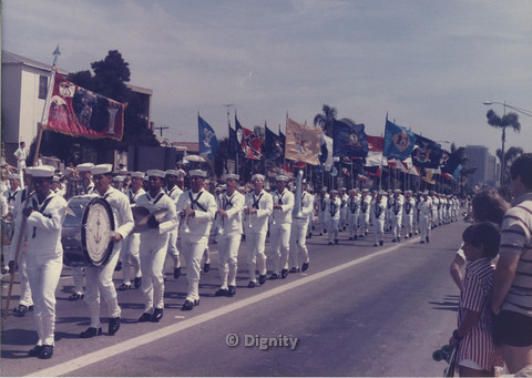 P104.136m.r.t Recruit Training Command San Diego at San Diego Pride Parade: Parade line of men in sailor outfits holding a variety of flags.