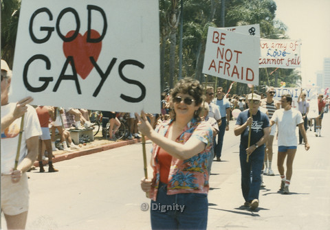 """P104.123m.r.t Dignity L.A. at San Diego Pride Parade: People marching in line with """"GOD <3 GAYS,"""" """"Be Not Afraid,"""" and """"An Army of Love Cannot Fail"""" signs prominent."""