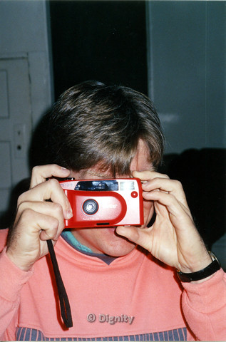P104.190m.r.t Dignity San Diego: Person holding red plastic Vivitar camera, taking a picture