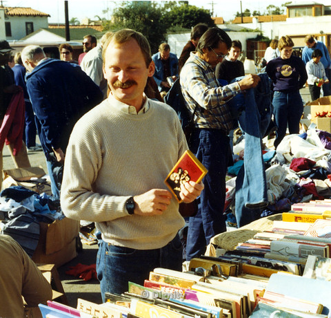 P104.156m.r.t Man holding book at book sale and clothing swap.