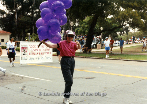 P024.427m.r.t 1990 San Diego Pride parade: Christine Kehoe marching in parade and holding balloons