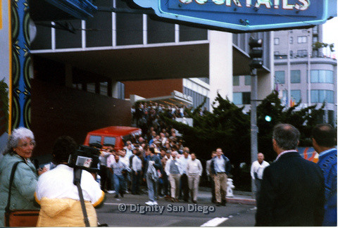 P103.139m.r.t Crowd of people exiting a building and crossing the street