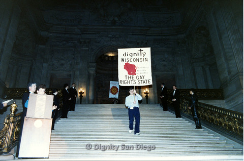 "P103.117m.r.t Dignity Ninth Biennial Convention 1989: Man walking down stairs while holding up sign ""Dignity Wisconsin, Northeast Madison Milwaukee, The Gay Rights State"""