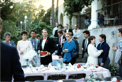 P103.155m.r.t Candid photo of people in formal attire standing around banquet tables outside. Bruce Neveu in tuxedo at left