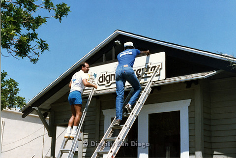 P103.165m.r.t San Diego Dignity Center: Two men on ladders finishing hanging sign at front of Center
