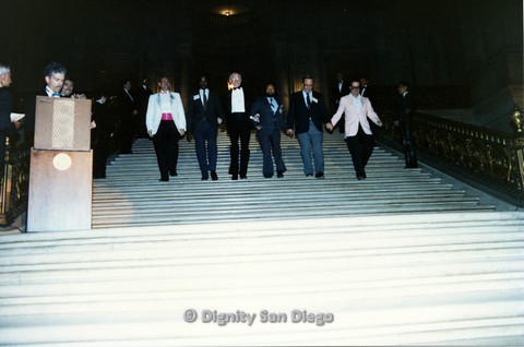 P103.118m.r.t Dignity Ninth Biennial Convention 1989: Men in formalwear, some holding hands, walking down stairs