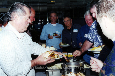 P040.056m.r.t SAGE General Meeting; group of men around the buffet table, two with nametags (from left to right: Charles and Robert)