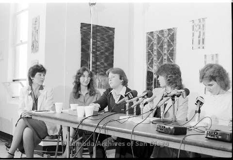 P123.023m.r.t Dixon Press Conference 1982:  (Left to Right) Diane Cooper (NOW/SD), Kim McAlister (CWSS), Robin Bruce, Fran Ledford, and Chris Russell looking at a talking Robin.